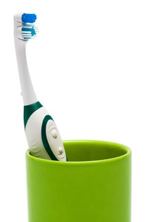 Toothbrush in a green glass on a white background photo