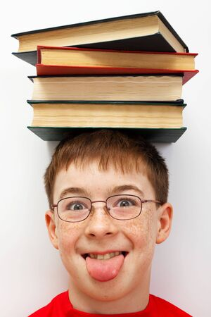boy with a pile of books on her head photo