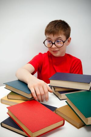 freckled boy in round glasses and a book photo