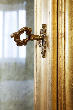 antique keyhole: golden key in the door a rich furniture