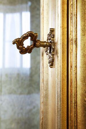 llave de oro en la puerta de un rico mobiliario Foto de archivo