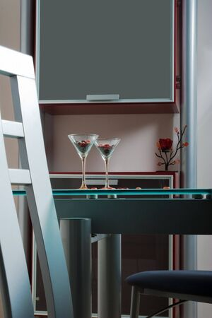 two wine glasses on a glass table in kitchen photo