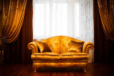 gold house: Beautiful sofa at a window in a modern apartment Stock Photo
