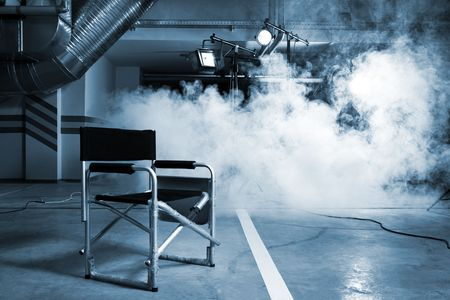 cinta pelicula: Silla para el director en el estudio sobre un fondo de un humo Foto de archivo