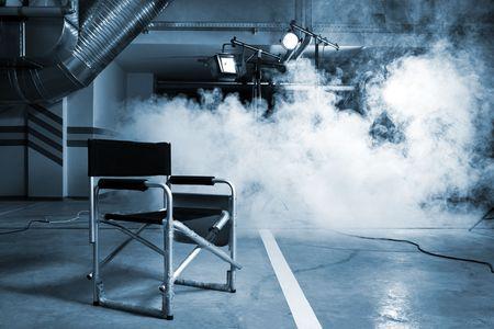 filmregisseur: Stoel van de bestuurder in studio op een achtergrond van een rook