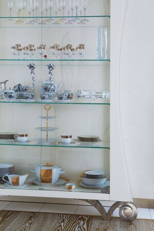 cabinet with beautiful dishes in a modern apartment photo