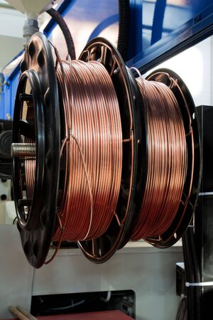steel cable: shiny copper wire on spools in the shop