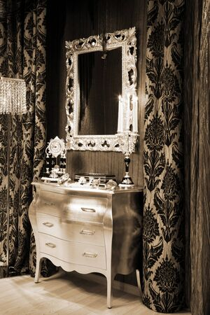 tallboy: mirror, a clock and burning candles in the candlestick Stock Photo