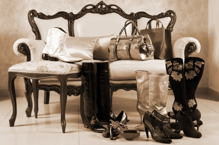 footgear: Female shoes, boots and handbags on a background of a sofa with pillows