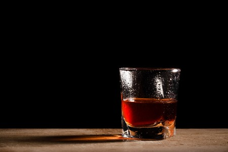 temperance: glass from whisky on a wooden table