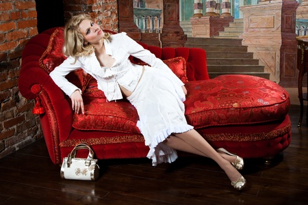 divan sofa: girl in a white dress on the red couch
