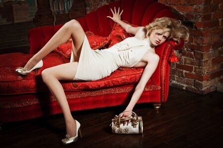 girl in a beige dress on the red couch photo