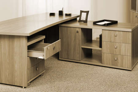 wooden desk with an open drawer in the office photo