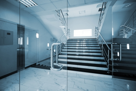 glass building: Glass doors with a kind on a marble staircase