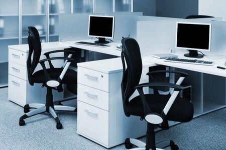 sedia vuota: computer sulle scrivanie in un ufficio moderno Archivio Fotografico