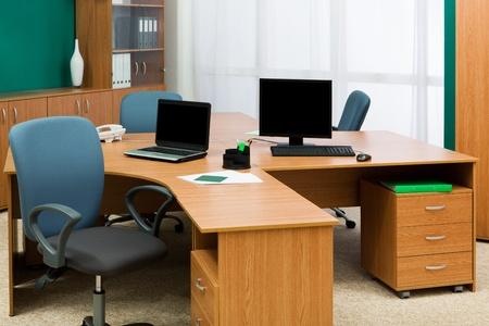 mobilier bureau: ordinateur et un ordinateur portable sur un bureau au bureau moderne Banque d'images