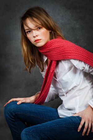 girl with a red scarf with a gray background photo