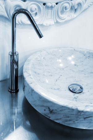 Marble sink and the metal tap in a bathroom photo