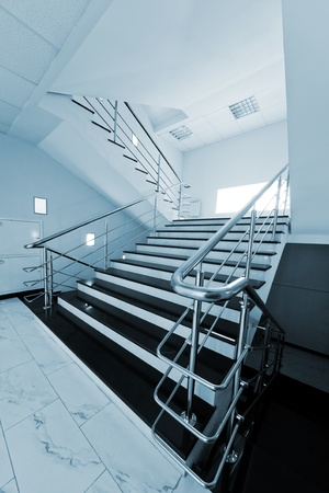 Marble staircase with a steel handrail in a modern building photo