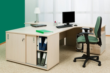 green office: laptop and computer on a desk in a modern office