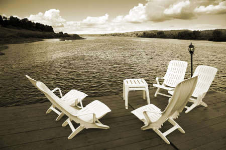Five white armchairs and table on coast of a reservoir Stock Photo - 9408016