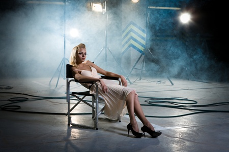 girl in a chair under the rays of searchlights photo