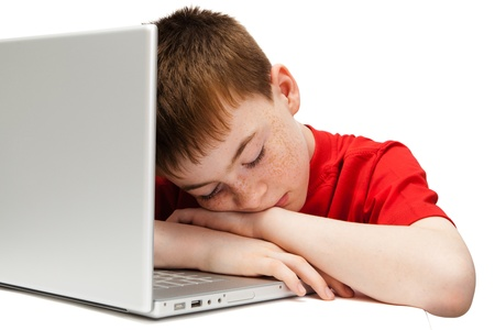 examination stress: sleeping boy with a laptop on a white background