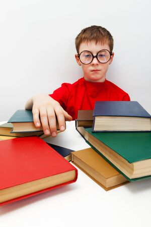 freckled boy in round glasses and a books photo