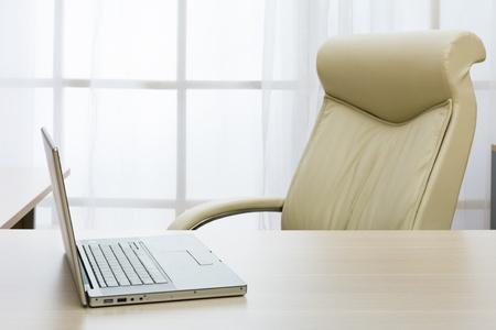 mobiliario de oficina: port�til en una tabla de director de oficina moderna Foto de archivo
