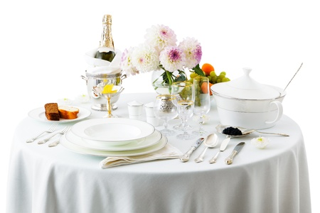 on the tablecloth: table with dishes and flowers on a white background