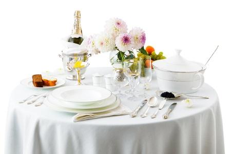 Tisch mit Speisen und Blumen auf weißem Hintergrund