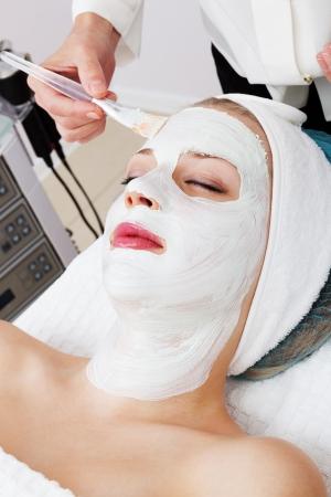 pulizia viso: posa di maschere cosmetiche in salone di bellezza moderna Archivio Fotografico