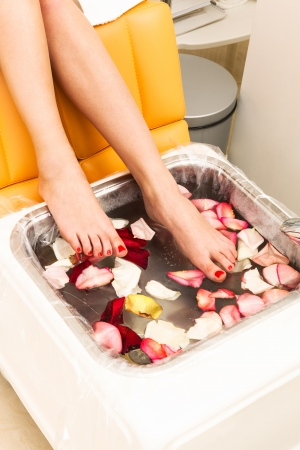 feet washing: bath with rose petals in pedicure Stock Photo