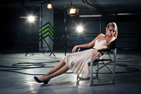 girl in a chair under the rays of searchlights