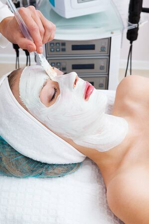 pulizia viso: posa in opera di mudpack in salone di bellezza moderna Archivio Fotografico