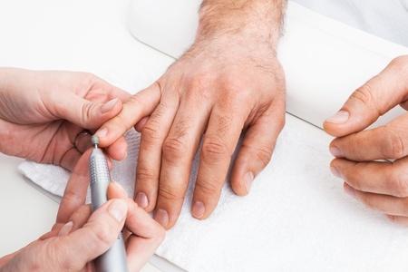 nail file: Manicure man close-up to the beauty salon