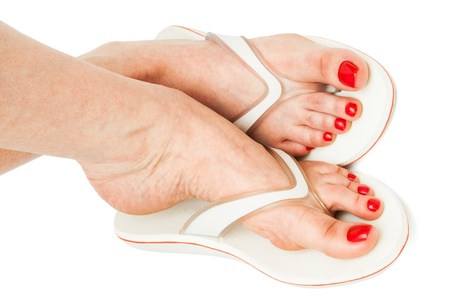 beautiful ankles: female feet in sandals on a white background
