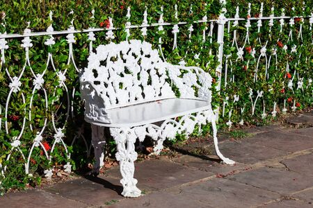 white wrought iron bench in the park photo