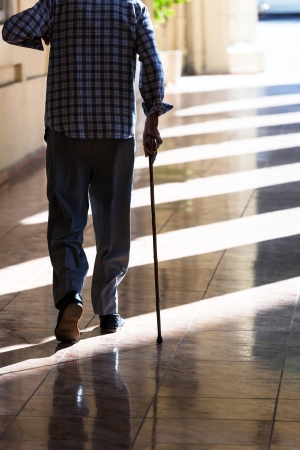 senior pain: an old man with a cane on the sidewalk