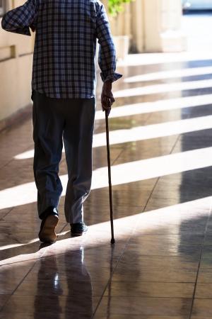 senioren wandelen: een oude man met een stok op de stoep
