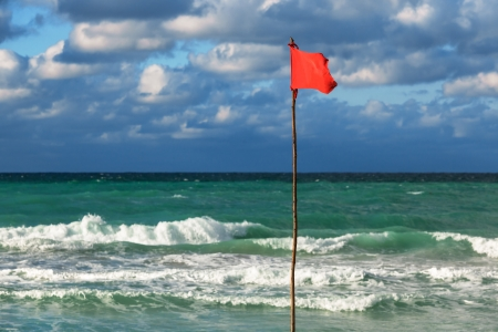 storm tide: red flag on the beach during a storm Stock Photo