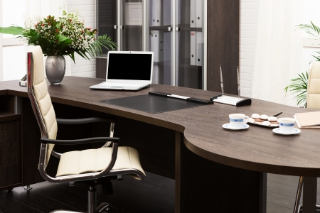 home office desk: laptop and flowers on the table in a modern office Stock Photo