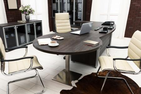 Laptop und ein Blumenstrauß auf einem Tisch im Büro Standard-Bild