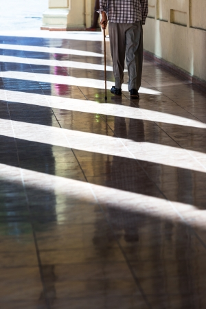 an old man with a cane on the sidewalk photo