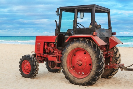 wheel tractor: old red tractor on the sandy beach Stock Photo