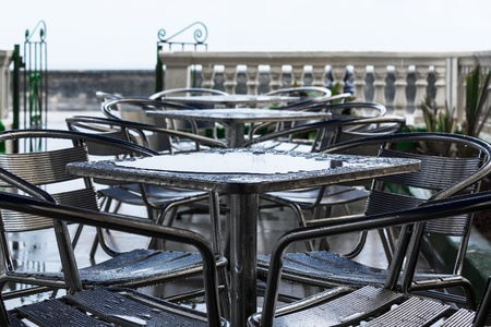 torrential: tables in the rain in a cafe on the street Stock Photo