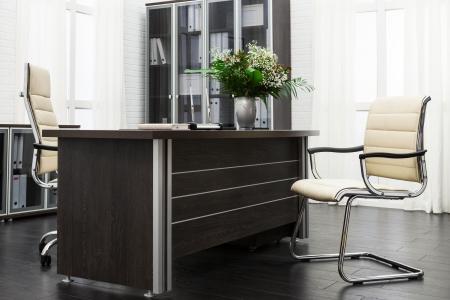 muebles de oficina: ramo de flores en un escritorio en la oficina moderna