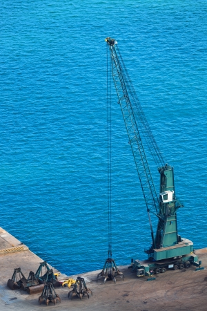 crane bucket: modern dredge in the harbor on a sunny day