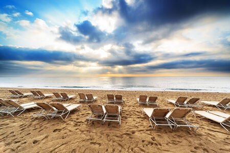 deck chairs on the beach at sunrise photo
