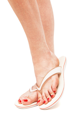 beautiful ankles: female foot in flip-flop on a white background